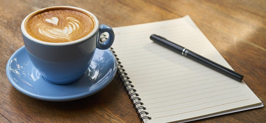 Coffee in a blue cup and saucer on a wooden table with a lined notepad and pen