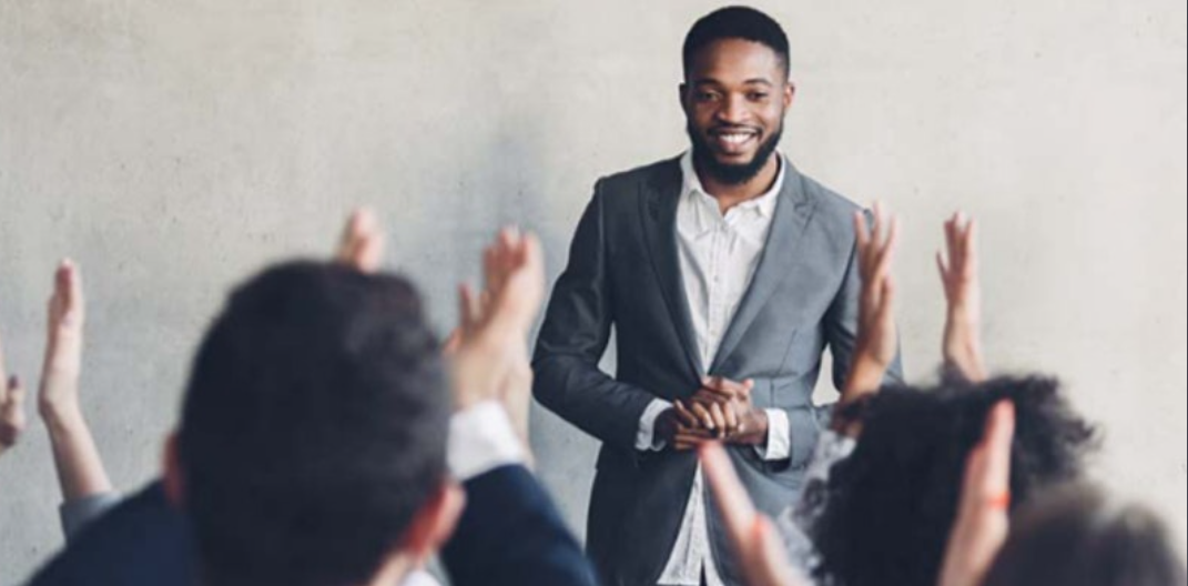 Male person of colour in grey suit standing in front of a room of people with raised hands