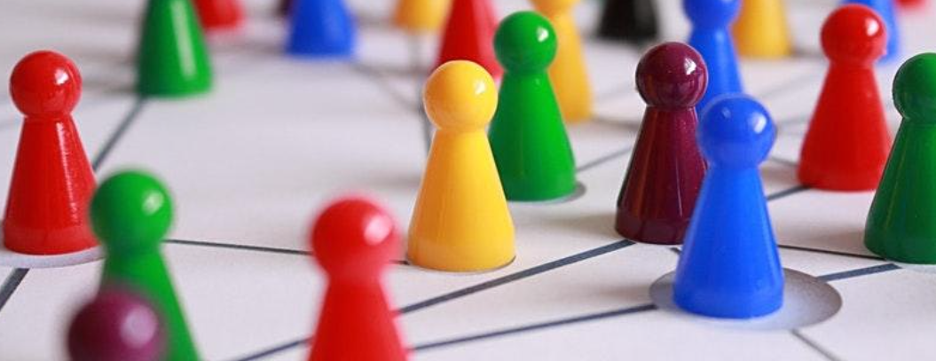 Multicoloured board game playing pieces connected by black netowrking lines on a white board